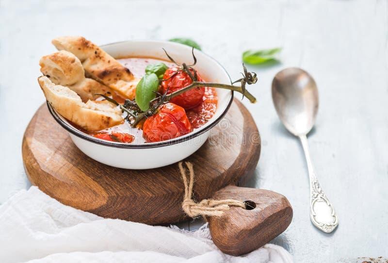 Włoski pomidoru, czosnku i basilu Pappa zupny al Pomodoro w metalu, rzuca kulą z chlebem na nieociosanej drewnianej desce nad bła obraz stock