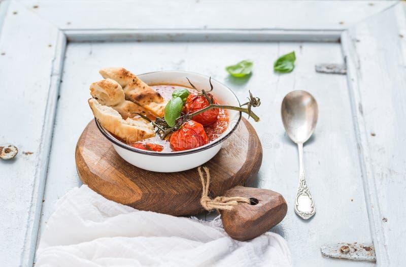 Włoski pomidoru, czosnku i basilu Pappa zupny al Pomodoro w metalu, rzuca kulą z chlebem na nieociosanej drewnianej desce nad bła obrazy stock
