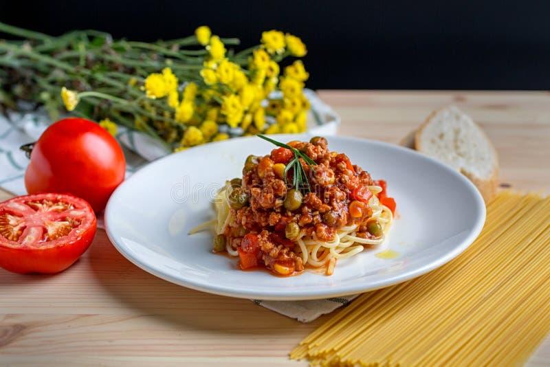 Włoski spaghetti z mięsnym zasadzonym kumberlandem w prostym bielu talerzu na drewnianym stole Spaghetti makaron z pomidorami fotografia royalty free