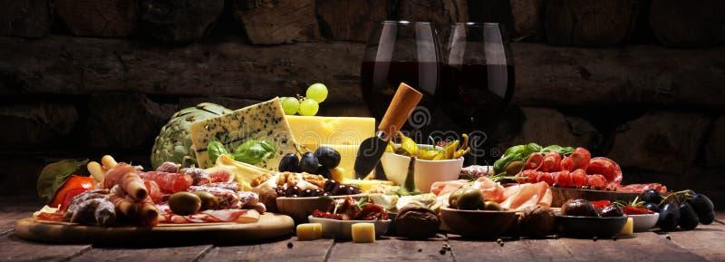 Włoskie antipasti wina przekąski ustawiać Serowa rozmaitość, Śródziemnomorskie oliwki, crudo, Prosciutto di Parma, salami i wino  zdjęcia stock