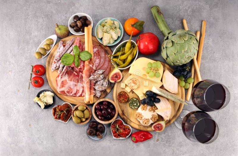 Włoskie antipasti wina przekąski ustawiać Serowa rozmaitość, Śródziemnomorskie oliwki, crudo, Prosciutto di Parma, salami i wino  zdjęcie royalty free
