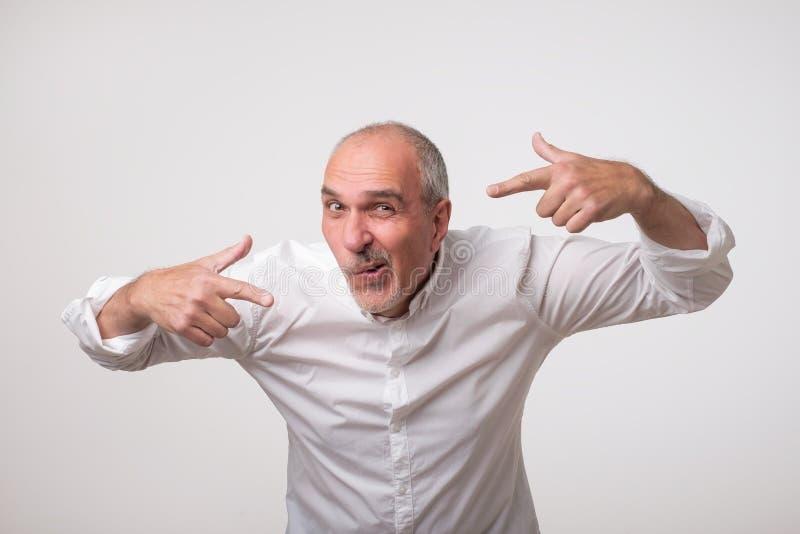 Włoskiego pozytywu dojrzały mężczyzna wskazuje on z palcami oba ręki w białej koszula, robi śmiesznemu grymasowi zdjęcia royalty free