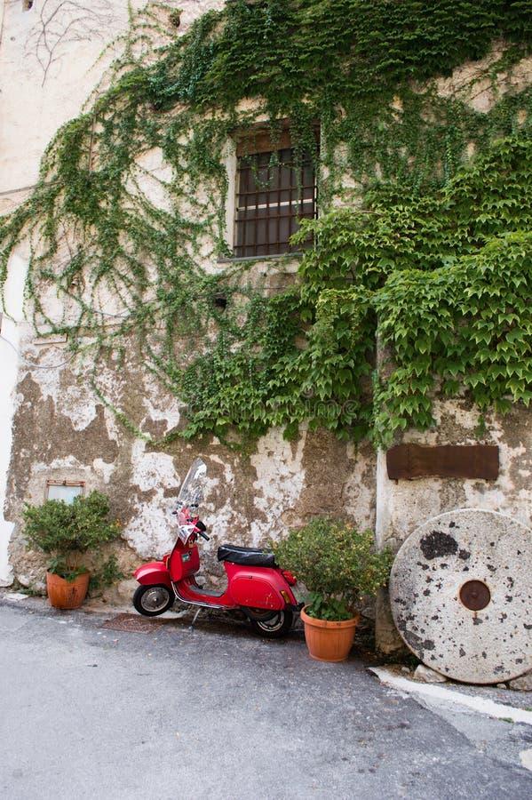 Włoskiego rocznika czerwona hulajnoga przed starym domem obraz stock