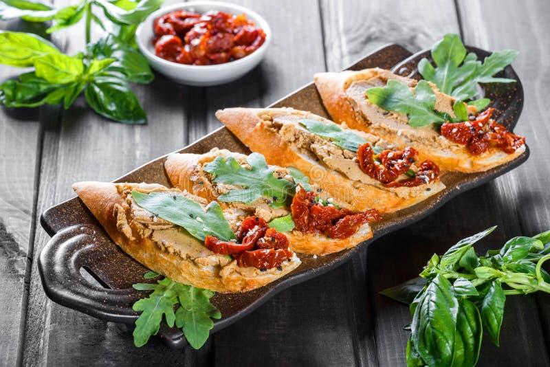 Włoszczyzna ściska - bruschetta z mięsnym łbem, arugula, słońca suszącymi ziarnami na ciabatta chlebie na ciemnym drewnianym stol zdjęcia stock