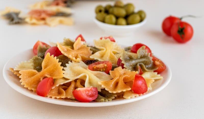 Włoszczyzna barwiący makaron z basilem i pomidory na zaświecamy talerza zdjęcie stock