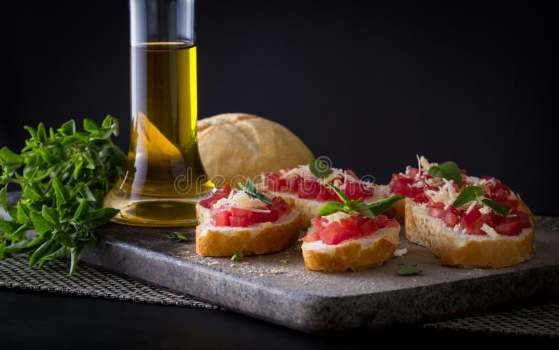 Włoszczyzna Bruschettas z pomidorami, basilem i oliwa z oliwek, zdjęcia stock
