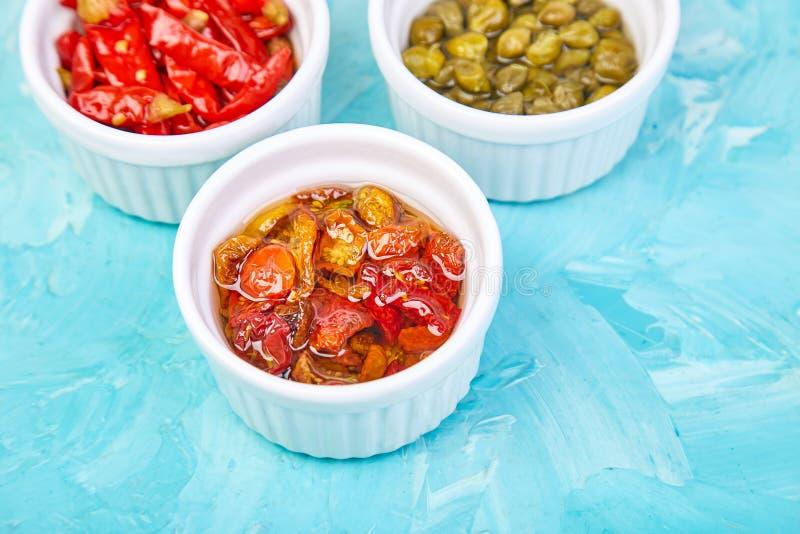 Włoszczyzna konserwujący set - marynowani kapary i pieprz, Sundried pomidory obraz stock