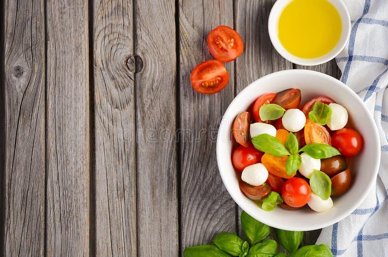 Włoszczyzny Caprese sałatka z czereśniowymi pomidorami, małą mozzarellą i świeżym basilem, zdjęcia stock