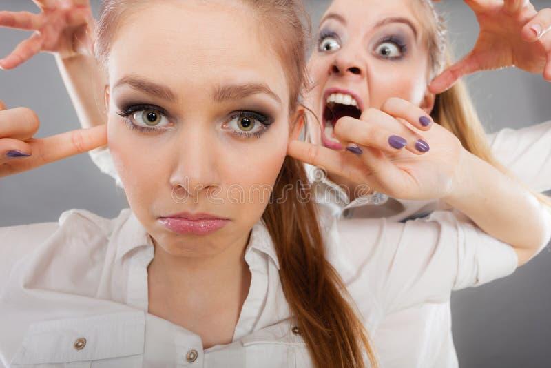 Wściekłości dziewczyna krzyczy przy jej przyjacielem, żeński przymknięcie jego ucho zdjęcie royalty free
