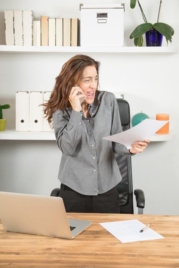 Wściekły bizneswoman krzyczy na wiszącej ozdobie z dokumentem w ręce zdjęcia stock