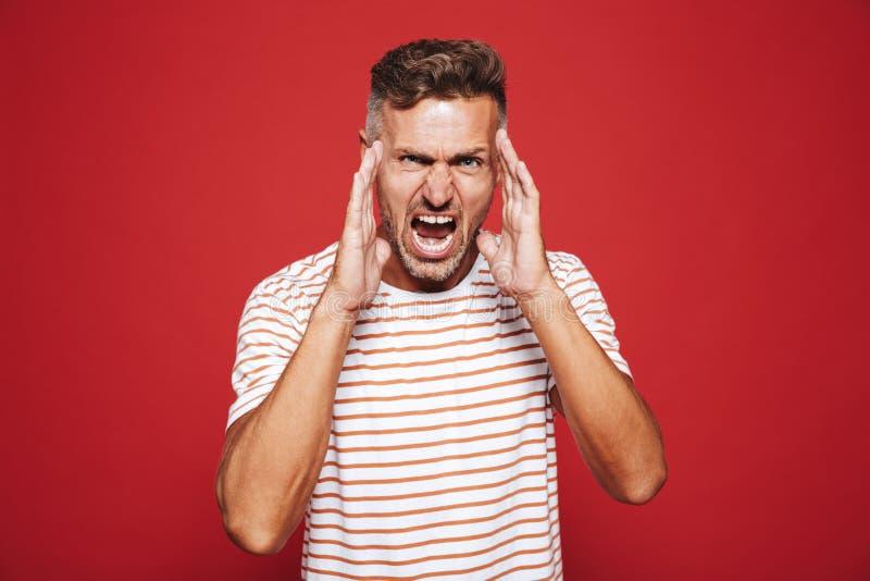 Wściekły dorosły mężczyzna krzyczy twarz i dotyka w pasiastej koszulce fotografia stock