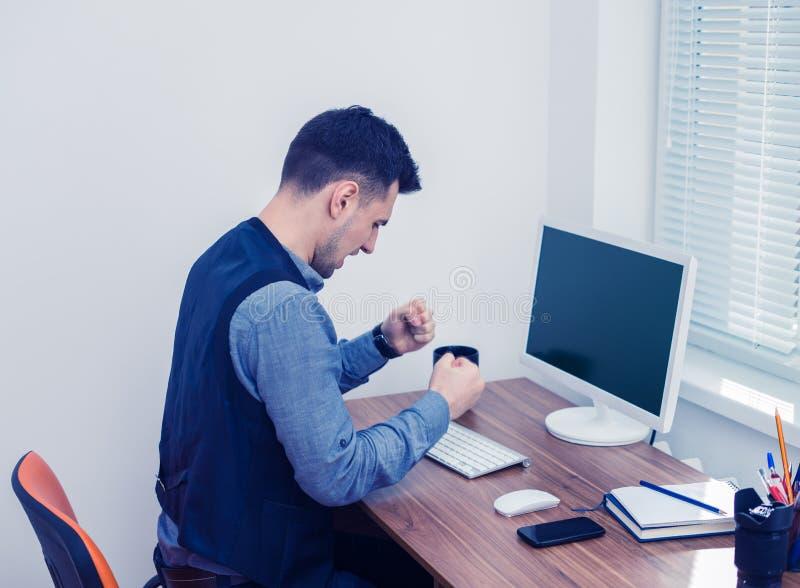 Wściekły młody biznesmen przygotowywający roztrzaskiwać jego komputer fotografia stock