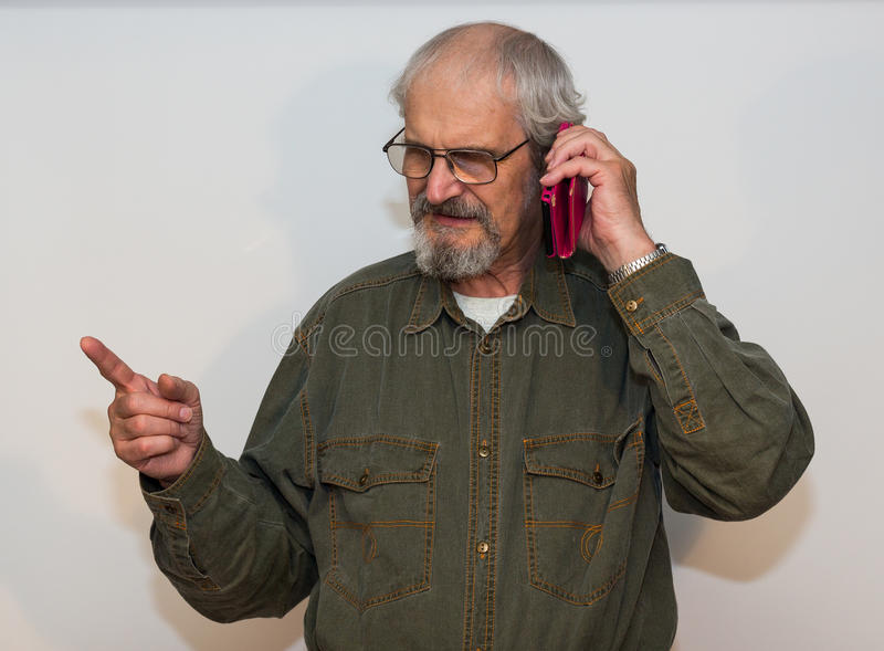 Wściekły starszy mężczyzna opowiada na telefonie zdjęcia stock