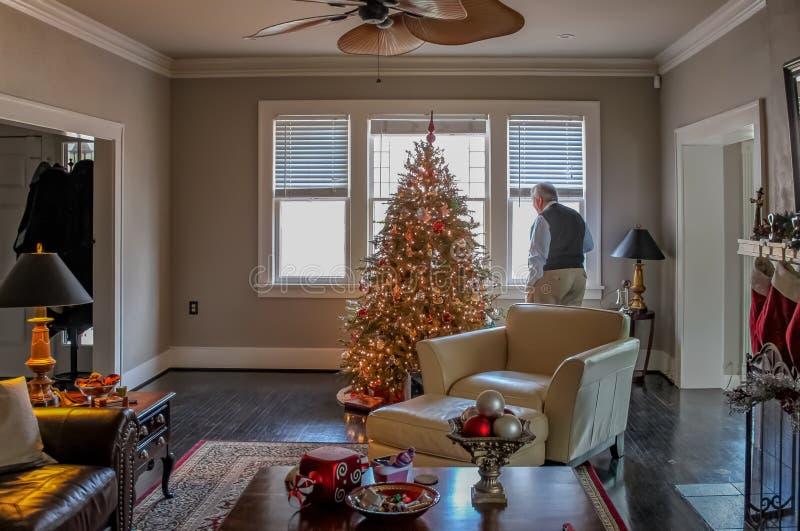 Wśrodku eleganckiego domu dekorującego dla bożych narodzeń z drzewem i pończochami stary mężczyzna patrzeje out okno zdjęcia stock