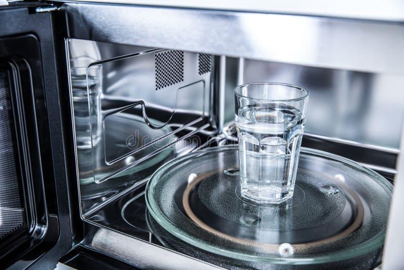 Wśrodku widoku nowy czysty staniless, mikrofala piekarnik z filiżanką czysta woda fotografia stock