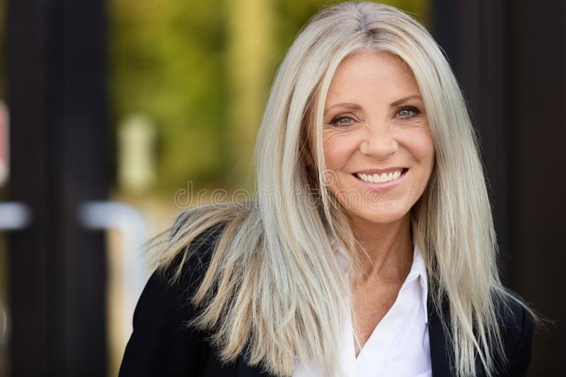 W średnim wieku kobieta ono uśmiecha się przy kamerą outside zdjęcie stock