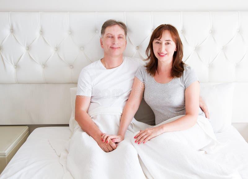 W średnim wieku starsza para w łóżku Rodzinny szczęśliwy związku mężczyzna, kobieta przy sypialni wnętrzem i Plciowy zdrowie i pr zdjęcia stock