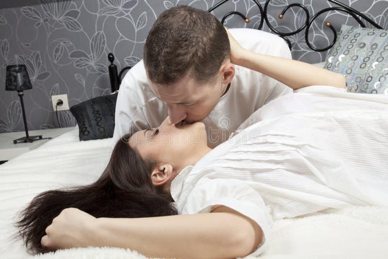 W łóżku mężczyzna i kobiety całowanie obrazy stock