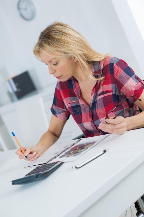 W średnim wieku żeński działanie przy biurkiem dalej w domu fotografia stock