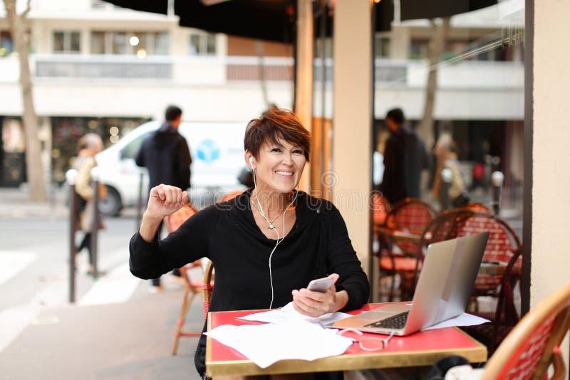 w średnim wieku żeński turysta słucha muzykę smartphone i danci zdjęcia royalty free