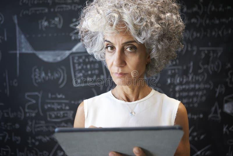 W średnim wieku akademicka kobieta używa pastylkę patrzeje kamera obrazy stock
