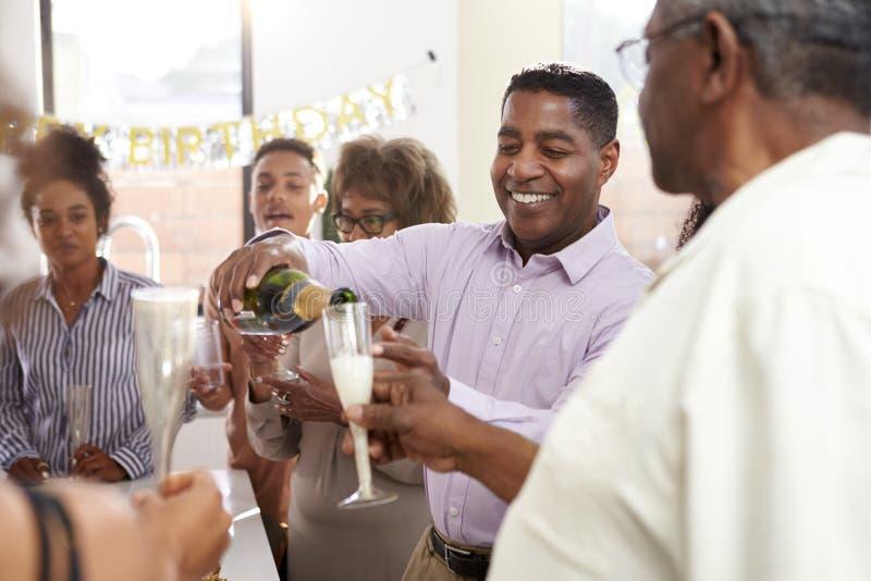 W średnim wieku amerykanin afrykańskiego pochodzenia mężczyzny dolewania szampan świętować z jego trzy pokoleń rodziną, zakończen obrazy stock