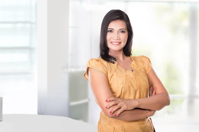 W średnim wieku Azjatycka kobieta ono uśmiecha się kamera, patrzeje szczęśliwy fotografia royalty free