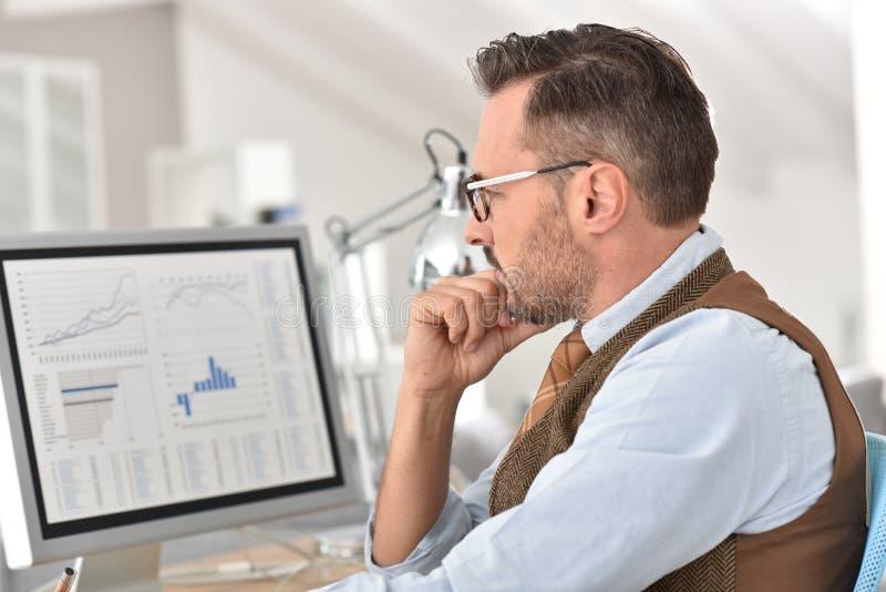 W średnim wieku biznesmen analizuje statystyki obraz stock