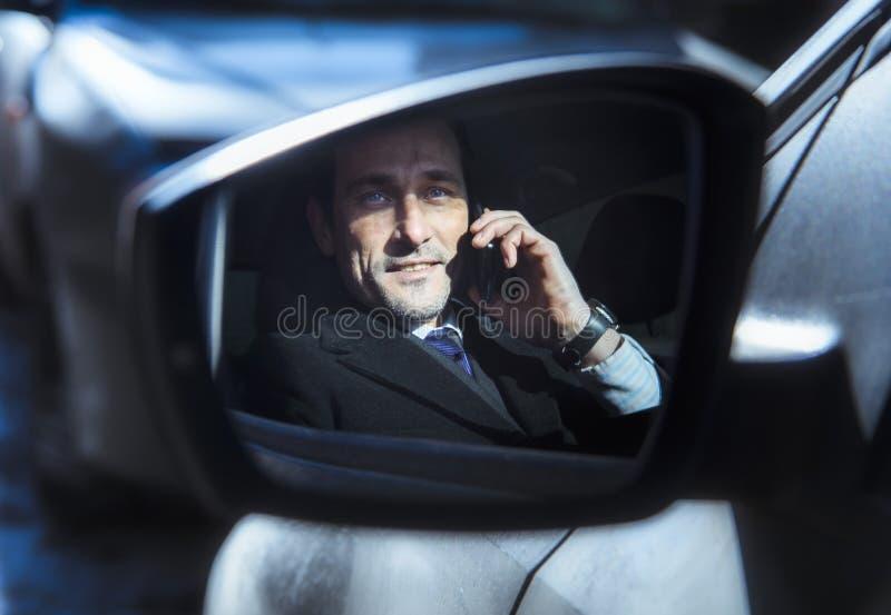 W średnim wieku biznesmen opowiada na telefonie, w swój samochodzie zdjęcie stock