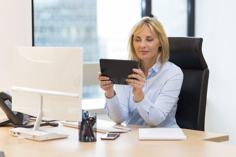 W średnim wieku biznesowa kobieta używa cyfrową pastylkę przy biurem obrazy royalty free