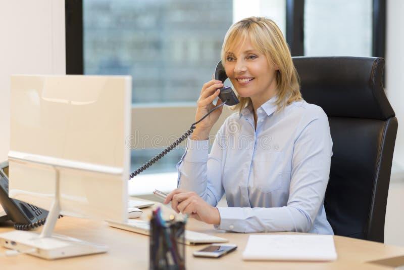 W średnim wieku biznesowa kobieta używa telefon przy biurem obrazy royalty free