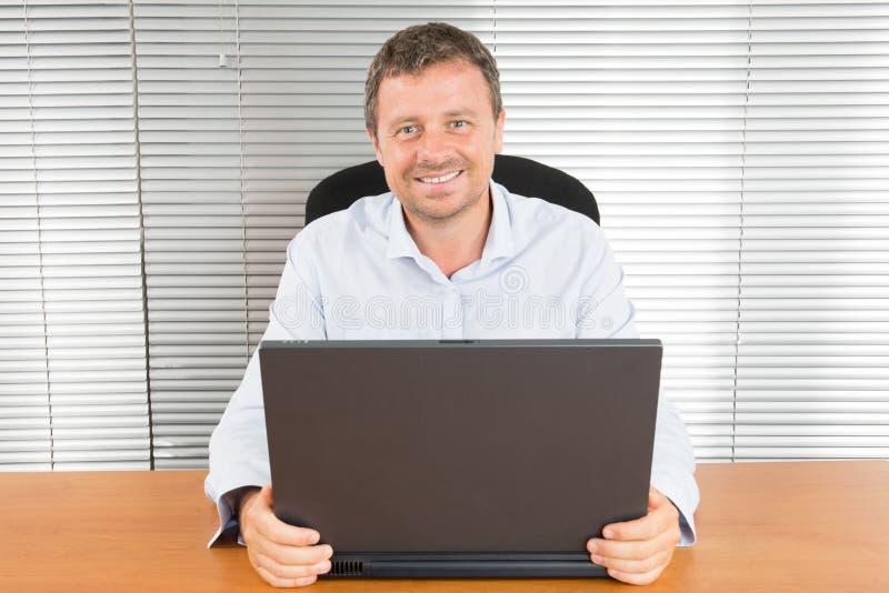 W średnim wieku biznesowy mężczyzna pracuje na laptopu biurowym biurku obraz royalty free