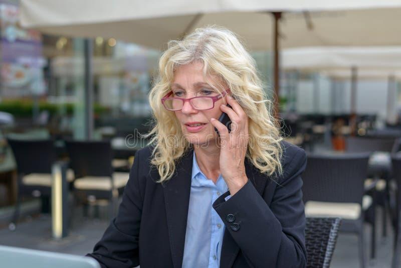 W średnim wieku bizneswoman opowiada na wiszącej ozdobie obraz stock