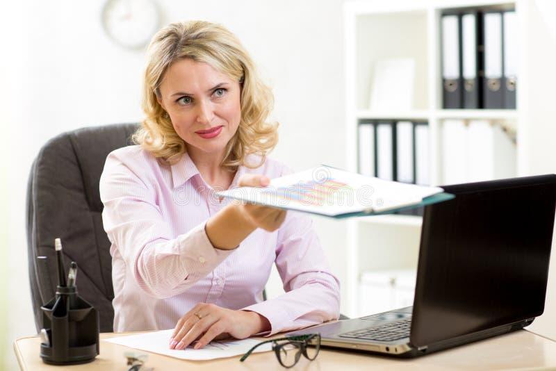 W średnim wieku bizneswoman pracuje w biurze i daje raportom obraz stock
