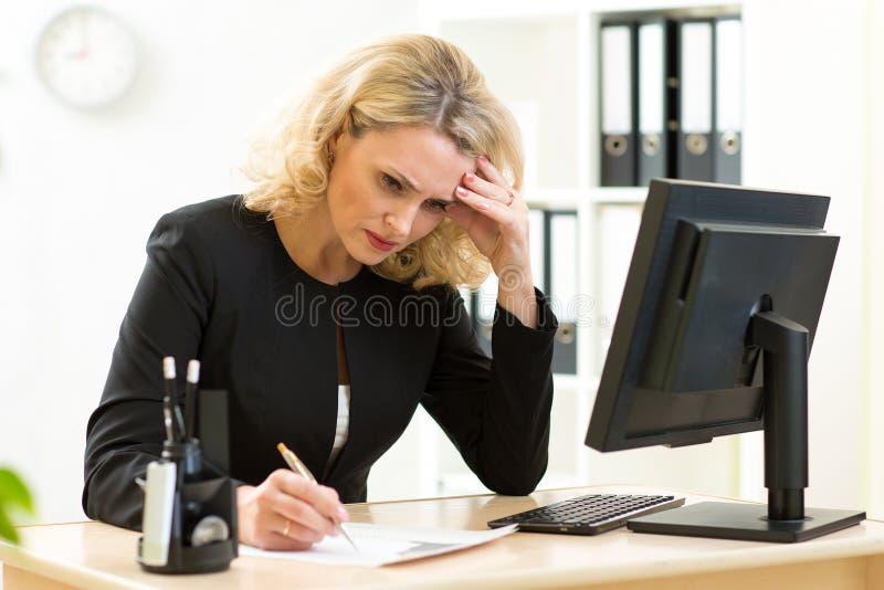 W średnim wieku bizneswoman pracuje w biurze i egzamininuje raporty obraz stock