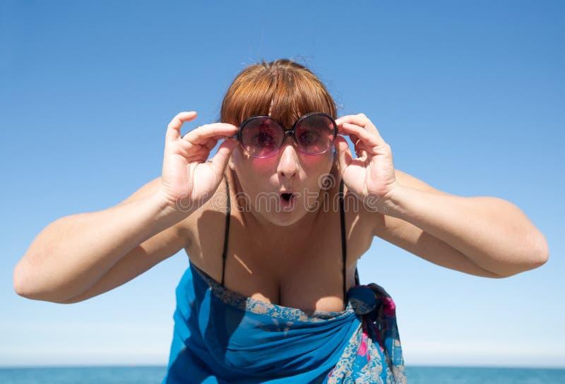 W średnim wieku kobiet spojrzenia przy kamerą przez zabarwiających okularów przeciwsłonecznych zdjęcia stock