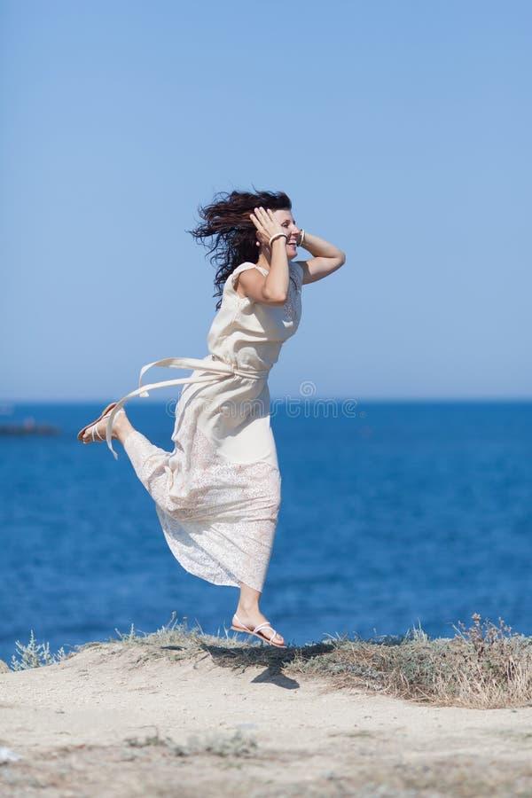 W średnim wieku kobieta w bielu smokingowy omijać wzdłuż seashore fotografia royalty free