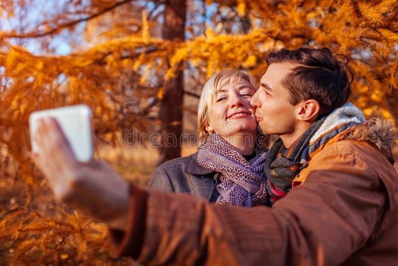 W średnim wieku kobieta bierze selfie z jej dorosłym synem używa telefon Wartości rodzinne zdjęcie stock