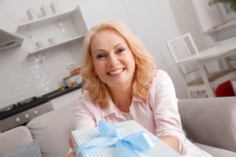 W średnim wieku kobieta czasu wolnego weekend lholding prezenta pudełko w domu zdjęcia royalty free
