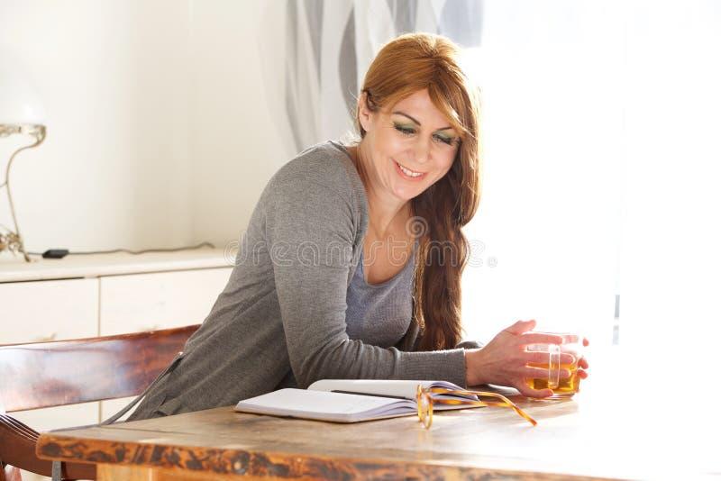W średnim wieku kobieta czyta książkę w domu zdjęcie stock