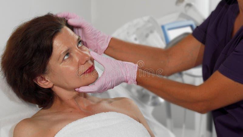 W średnim wieku kobieta dostaje ona skórę egzamininująca dermatologiem obraz stock