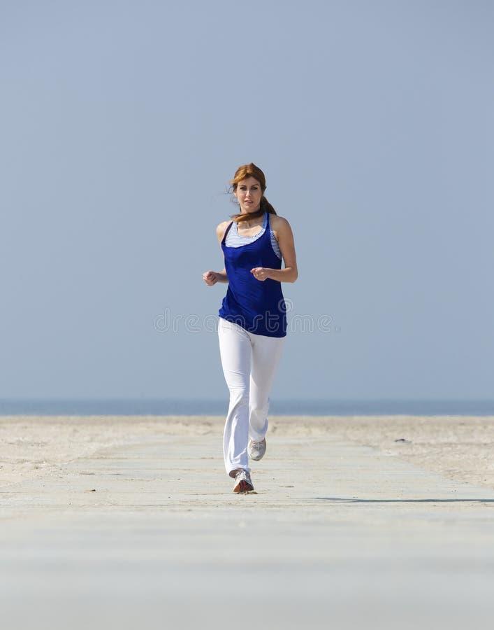 W średnim wieku kobieta jogging przy plażą zdjęcie royalty free