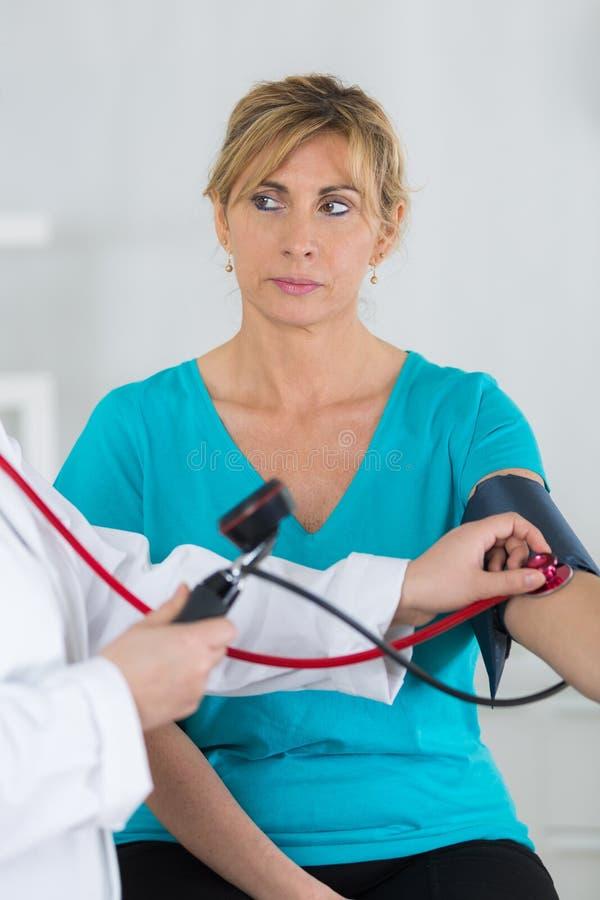 W średnim wieku kobieta ma ciśnienie krwi sprawdzać zdjęcie stock