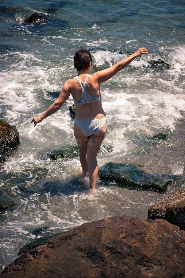 W średnim wieku kobieta na skalistej plaży obraz royalty free