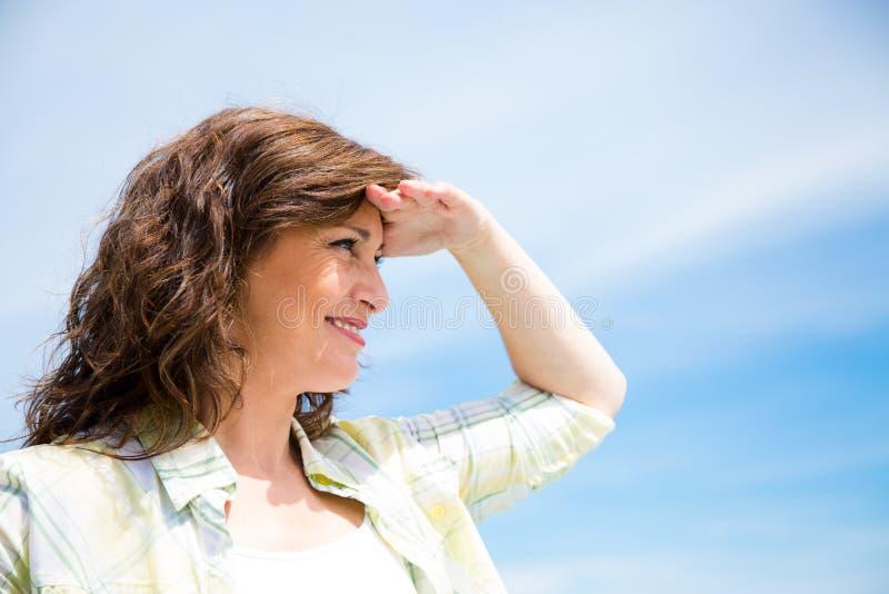 W średnim wieku kobieta patrzeje naprzód zdjęcia stock