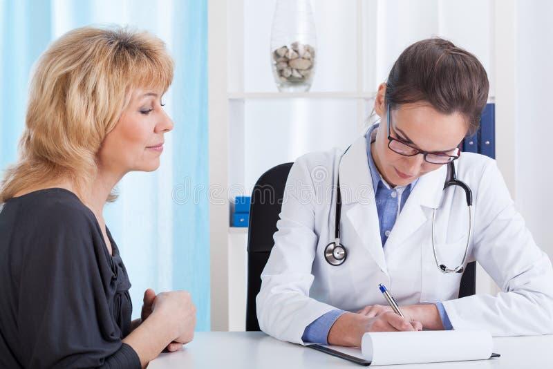 W średnim wieku kobieta podczas medycznego spotkania zdjęcia stock