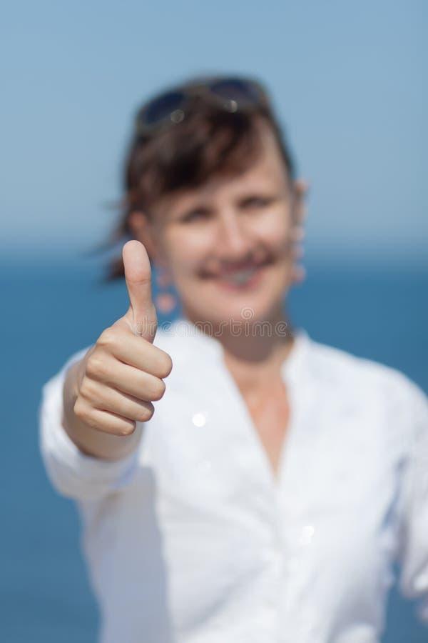 W średnim wieku kobieta pokazuje kciuk up obrazy stock