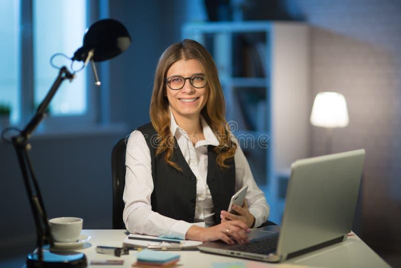 W średnim wieku kobieta pracuje w biurze do noc na jawnym obraz stock