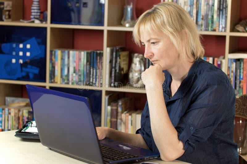 W średnim wieku kobieta pracuje od domu zdjęcia royalty free
