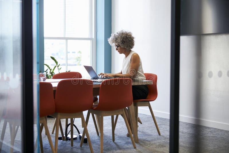 W średnim wieku kobieta pracuje samotnie w biurowej sala posiedzeń zdjęcia stock